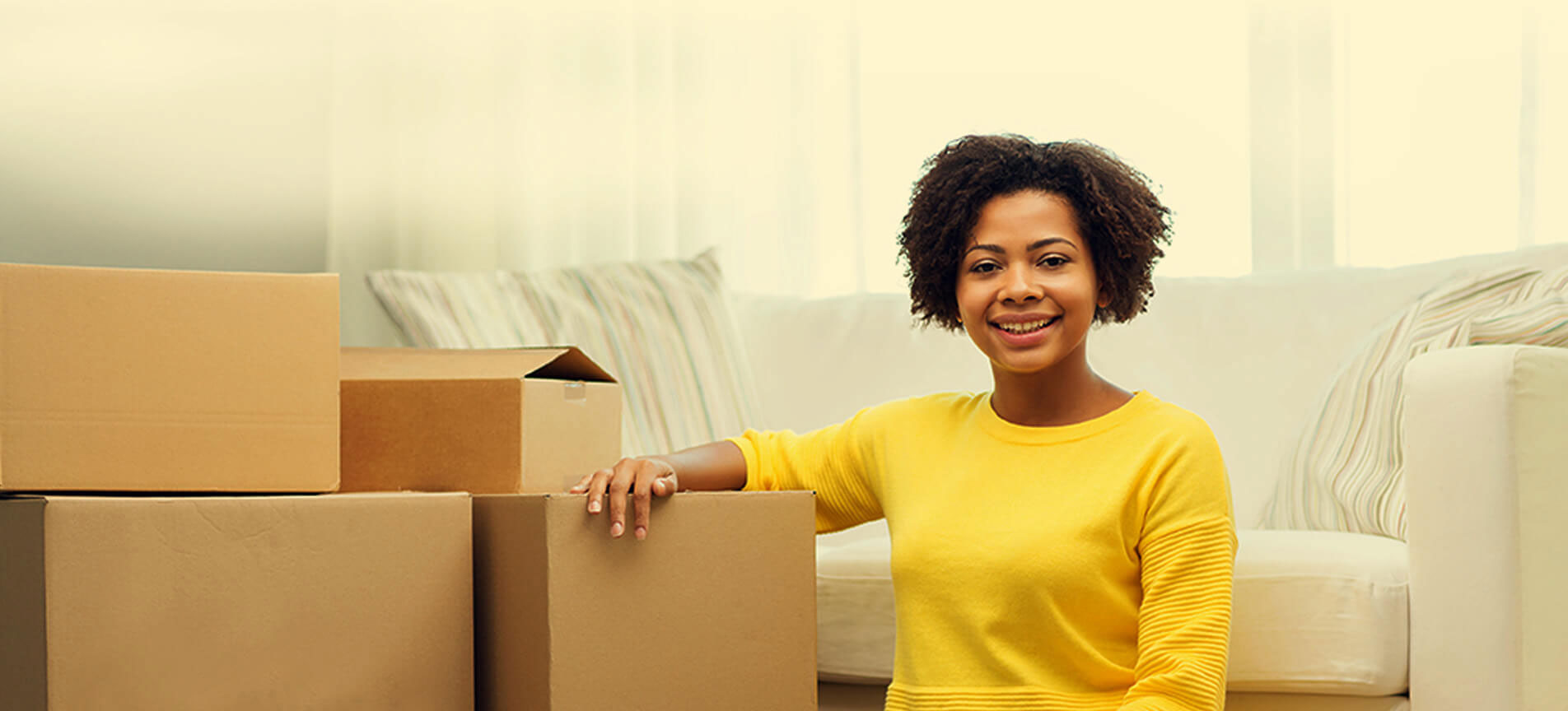 Image of a woman sitting by packed boxes in a living room.